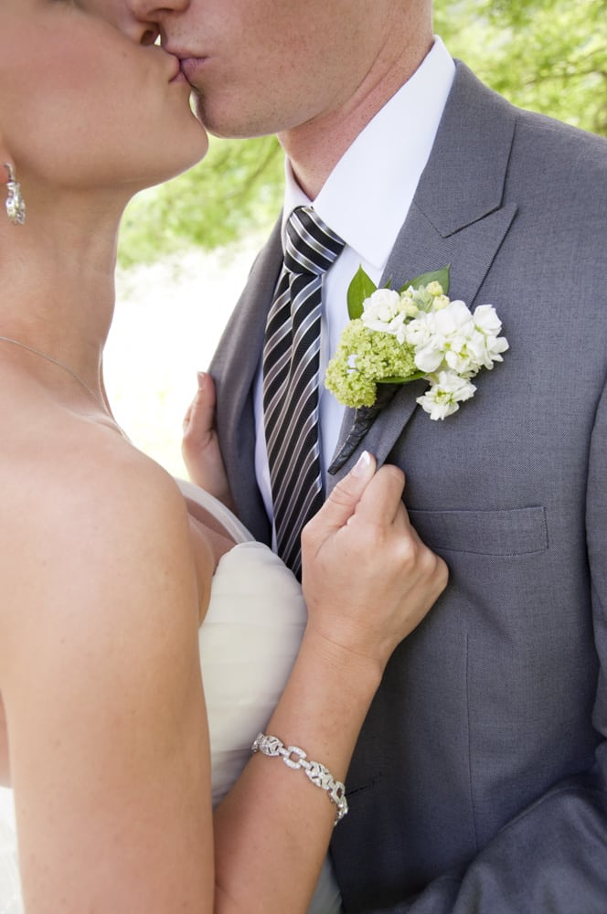 wedding couple details with bracelet, boutineer, ear ring, tie, and kiss in South County