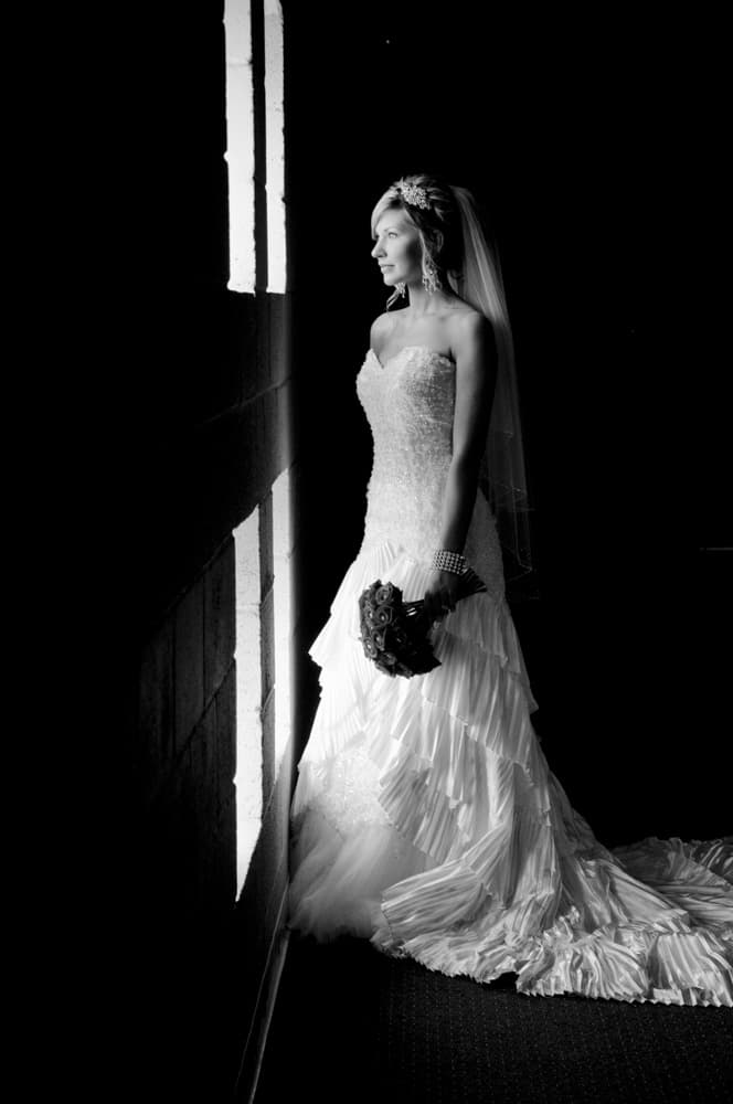 Bride looking outside of window with wedding dress details