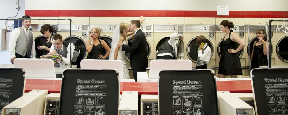 panoramic picture of wedding party at a laundromat posing like they are doing their laundry