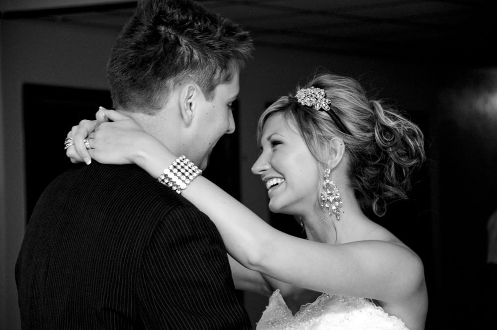 Bride smiling while dancing with her new husband at reception