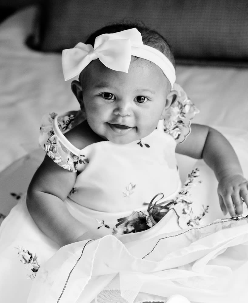 Baby flowergirl smiling with bow in her hair