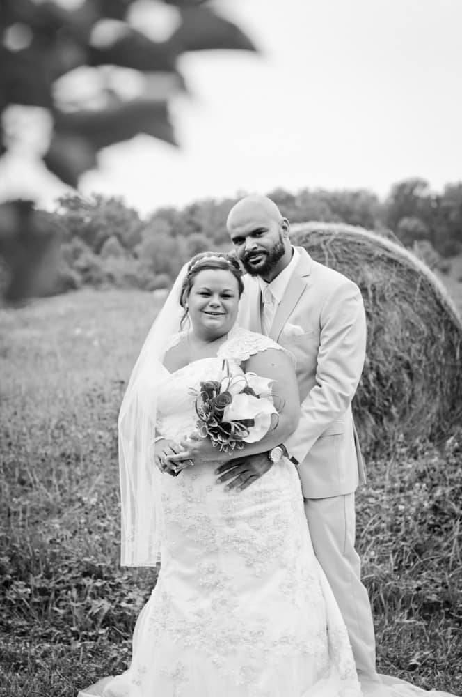 Bride and Groom posting near a bale of hay in an orchard in Indiana right before a wasp attack