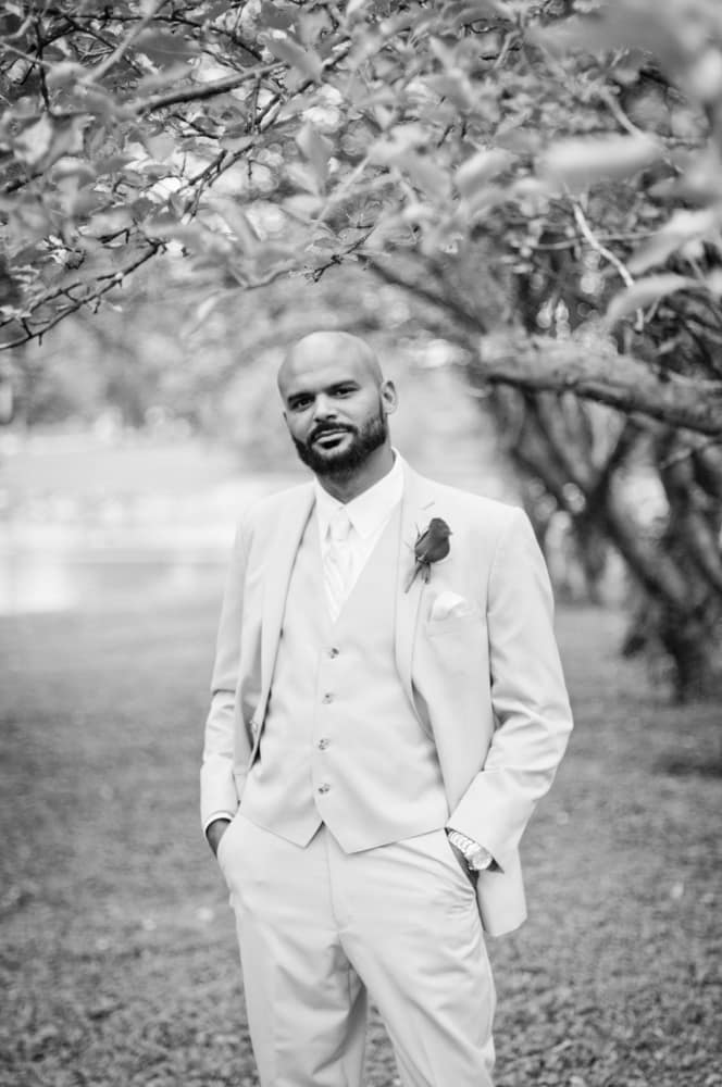 African American vetran groom on wedding day in orchard outside of Indianapolis
