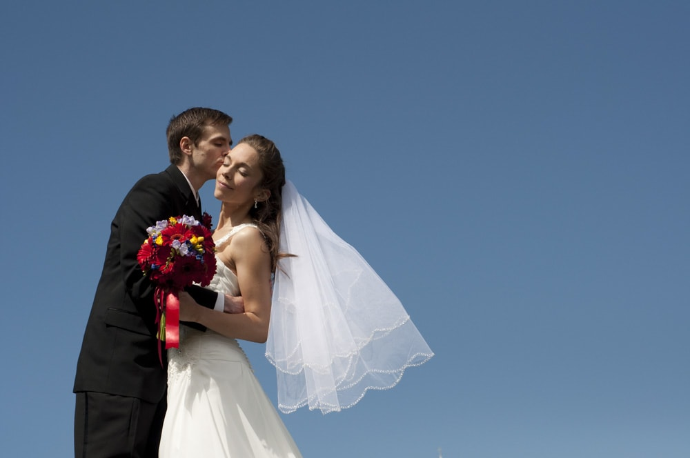 Bride's short veil blowing in the wind with husband kissing her with blue sky in West County Saint Louis