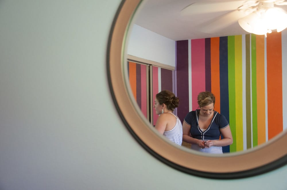 bridge and bridesmaid doing makeup in childhood bedroom with bright colorful stripes
