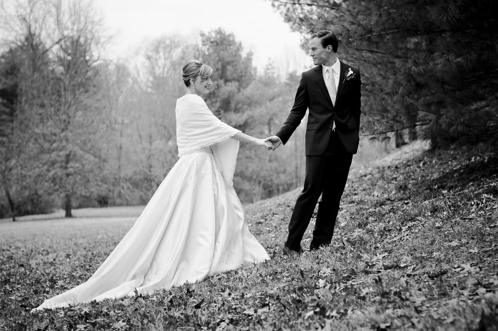 Groom leads bride with shawl up a hill on their wedding day in the winter in Town and Country