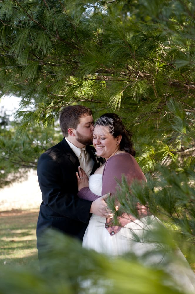 couple kissing in picture from winter wedding with bride wearing cardigan sweater and short veil in pine trees in Lincoln IL