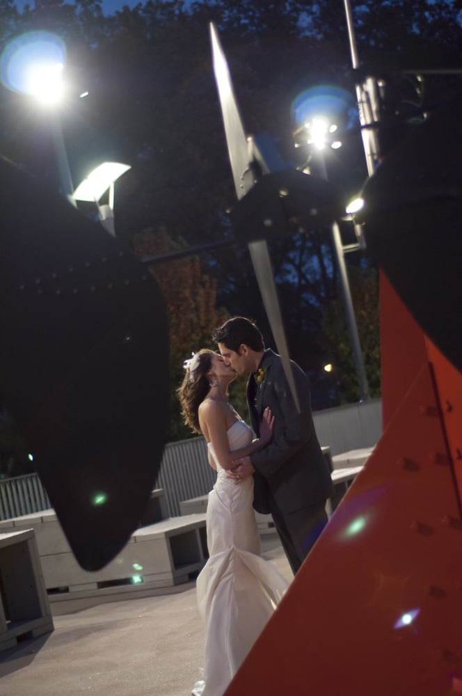 bride and groom kissing outside at night at Washington University near art museum