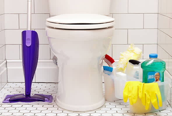 A clean bathroom with bucket of cleaning supplies including Swiffer and Mr Clean