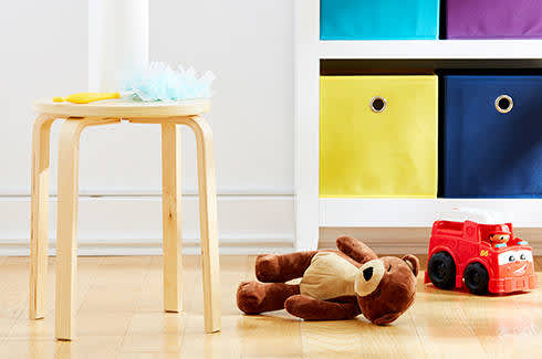 A kids playroom with a duster and some toys on the ground