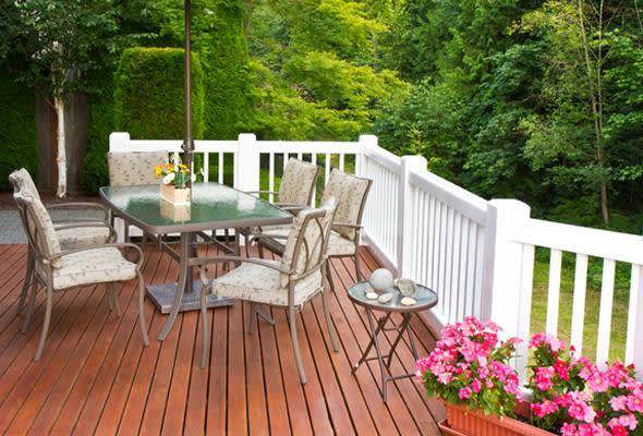 A backyard deck with a table and pretty flowers
