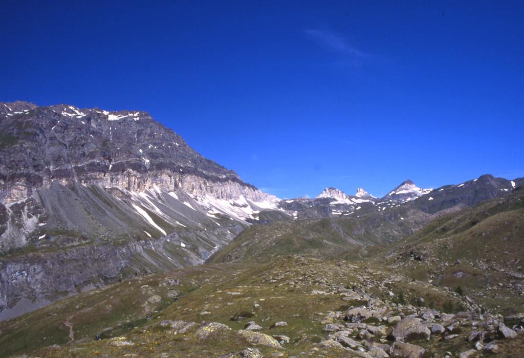 06. Sul versante destro del vallone appare la fascia bianca sopra la quale poggia il livello superiore dell'antico fondo oceanico con le rocce in prevalenza derivate da sedimenti d'alto mare.