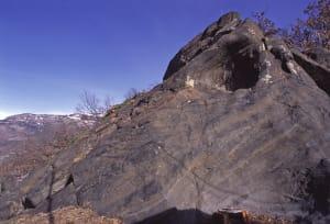10.Le rocher noir de Chadel avec « marmite » d'érosion sous-glaciaire. Il s'agit d'une métabasite en faciès éclogite, avec omphacite et grenat.