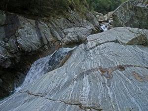 La pasta rocciosa stirata e trasposta per chilometri si è deformata in una infinita successione di livelletti paralleli e uniformemente orientati, in giacitura pressoché verticale