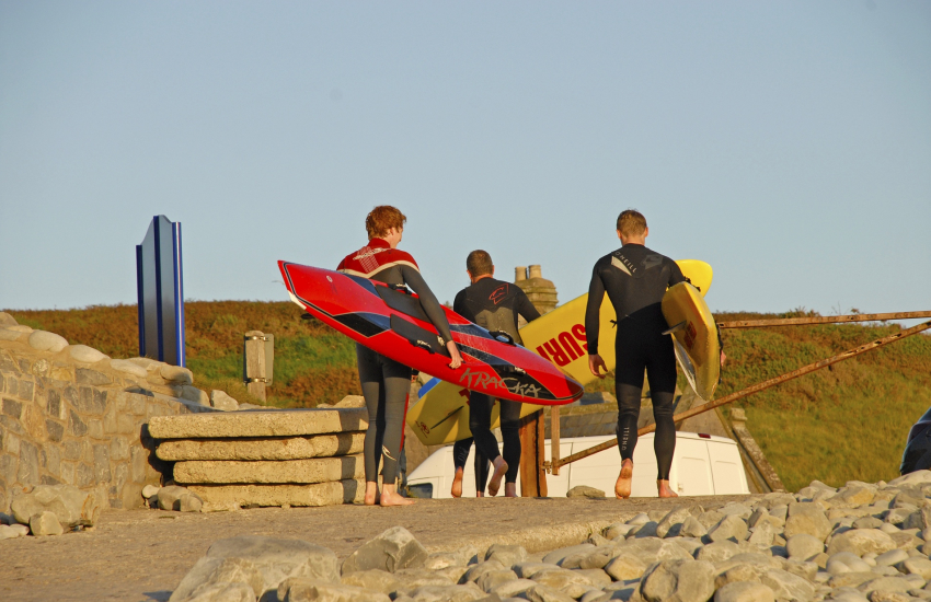 Water-sports enthusiasts surf boards and wetsuit hire