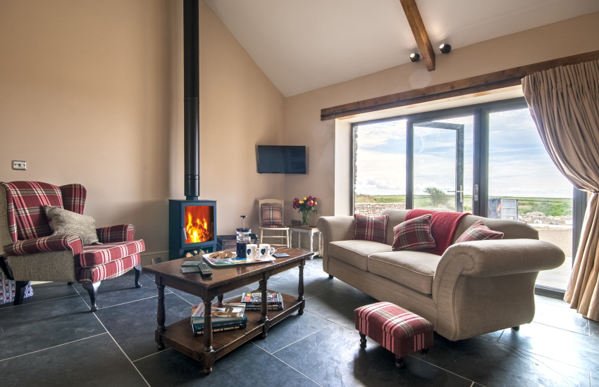 St Davids holiday cottage - sitting room with log burner and Bi-fold doors to patio