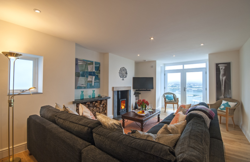 Sitting room with log burner and balcony with harbour views
