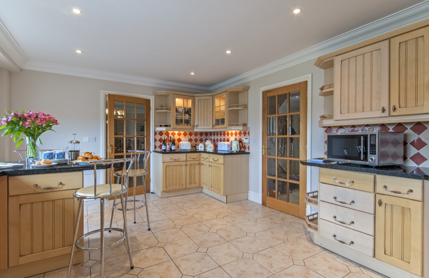 Modern fitted kitchen with breakfast bar and valley views