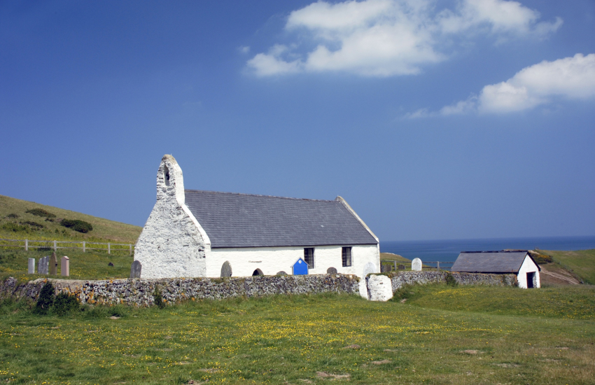 15th century Church of the Holy Cross sits high on the cliffs overlooking the beach at Mwnt