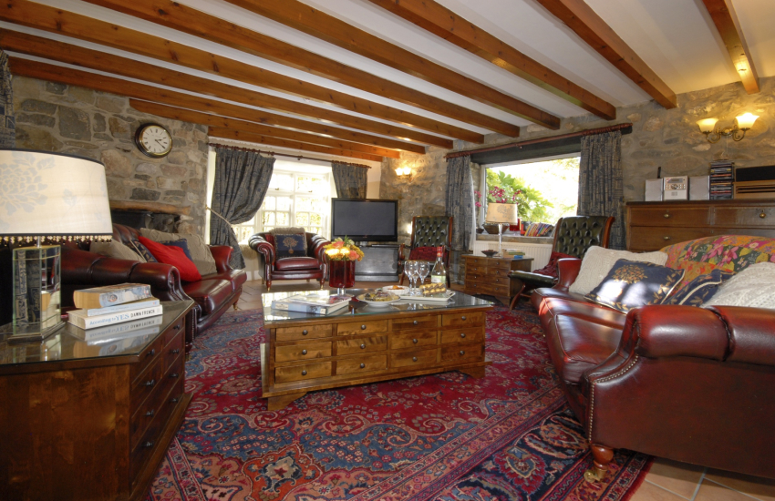 Solva traditional holiday cottage sitting room with beamed ceiling and open fire