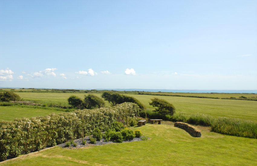 Views from the master bedroom over the gardens to the coast beyond
