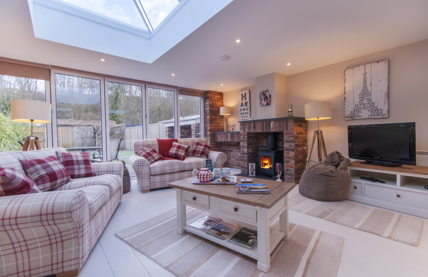 Luxury open plan living room with wood burner and Bi-fold doors to the garden