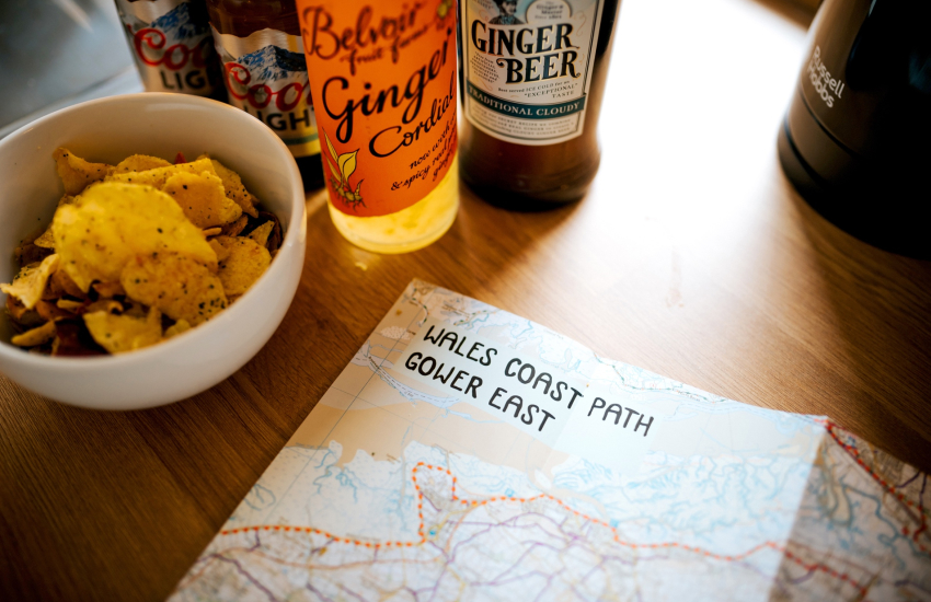Kitchen table map of Gower coast and bottles of ginger beer
