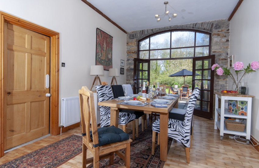 Oxwich Bay holiday home - dining room with glass doors to gardens