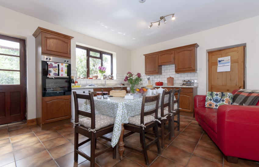 Gower, self-catering family home - fully equipped kitchen with sofa and table seating 8
