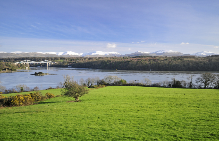 The Menai Suspension Bridge with snow capped Snowdonia beyond