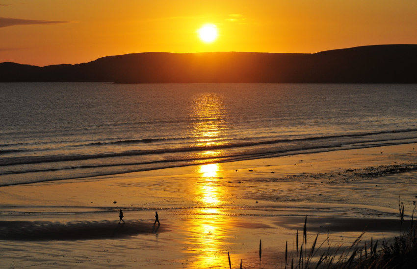 Setting sun over Newgale Sands and Ramsey Island beyond