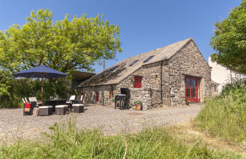 Pet friendly St Davids holiday barn - garden area with rattan furniture and BBQ