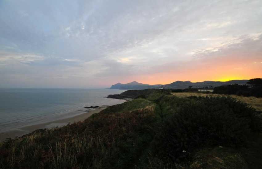 The sun rising behind the mountain at Nefyn