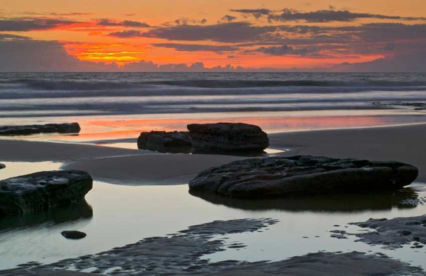 Enjoy glorious sunsets down on the beach at Dunraven Bay.