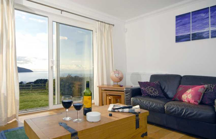 Coastal home for holidays - lounge with stunning sea views through the patio doors