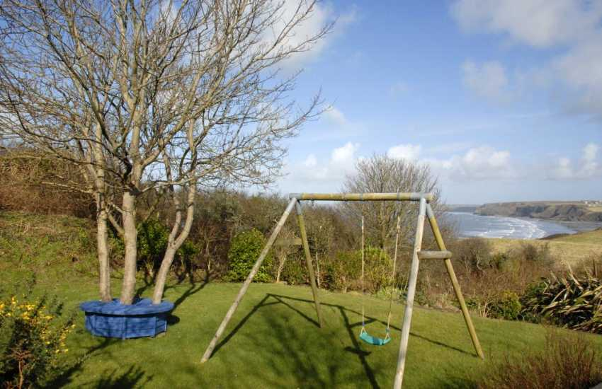 Pembrokeshire holiday home with children's play area in the garden with sea views