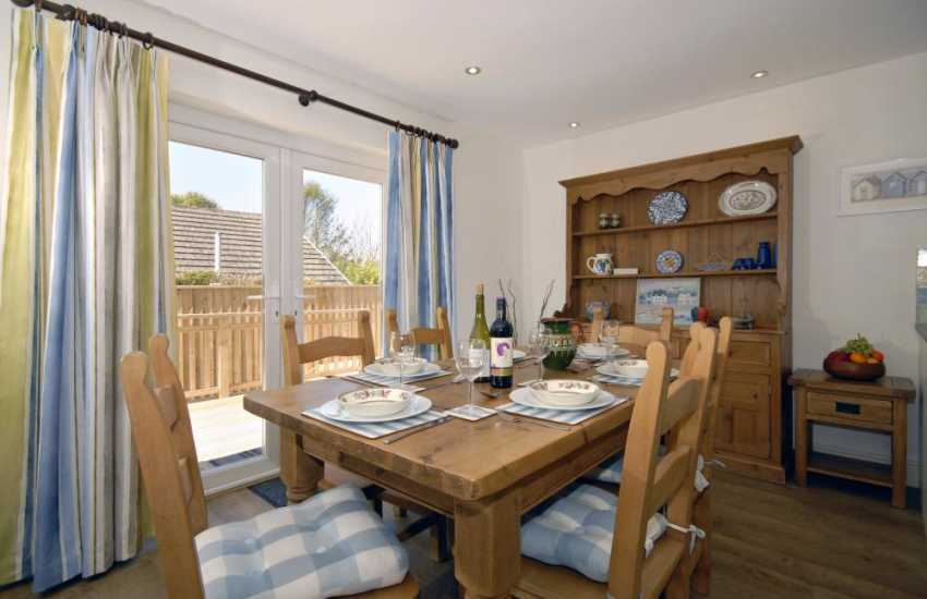 Manorbier holiday bungalow - dining area with patio doors to South facing deck
