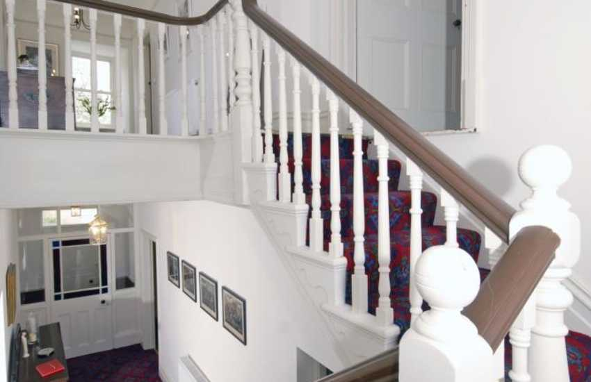 The elegant turning staircase in the hallway has Victorian stained glass windows and a display of paintings by a local artist