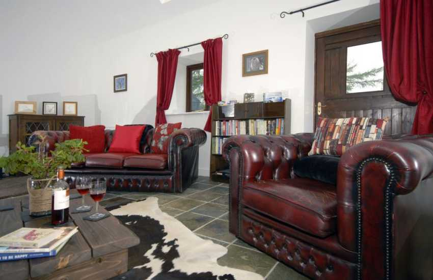 Newcastle Emlyn holiday home with comfy leather sofas and a variety of colourful canvas pictures throughout