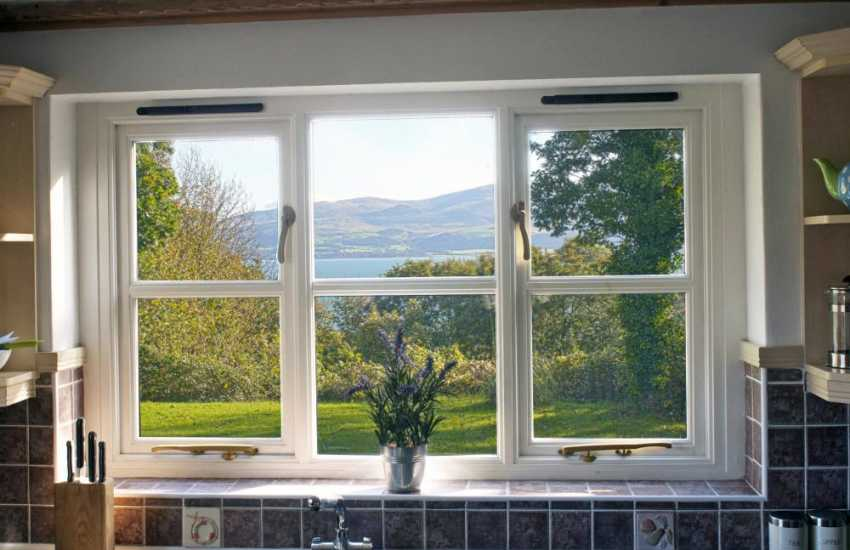 Views over a woodland clearing and Menai Strait to Snowdonia beyond