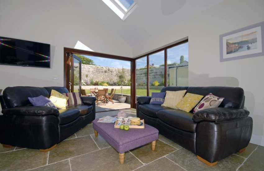 Whitesands self-catering cottage - family sitting room with bi-fold doors opening to enclosed gardens