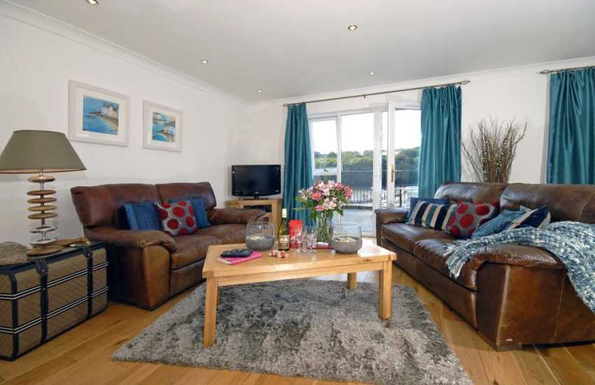 Pembrokeshire Haven Waterway luxury holiday home - open plan living room with doors to terrace and river views