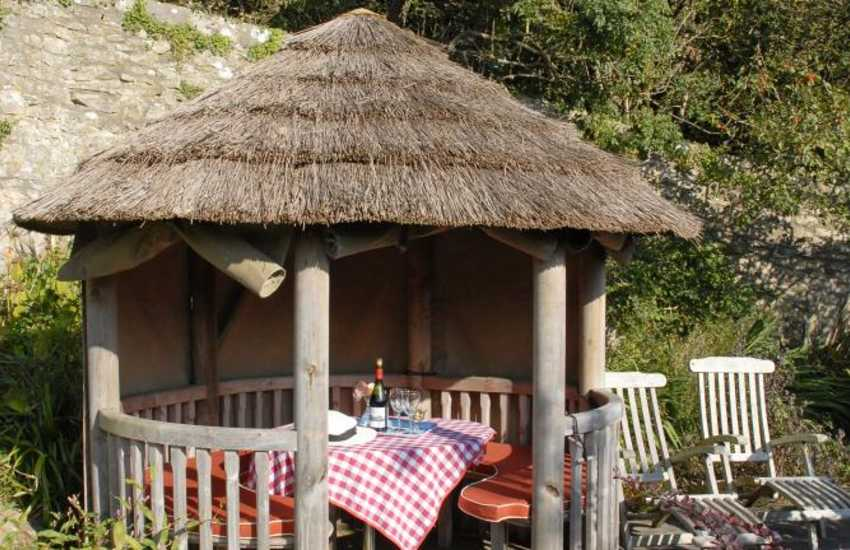 Escape to the little thatched gazebo in the gardens of the estate