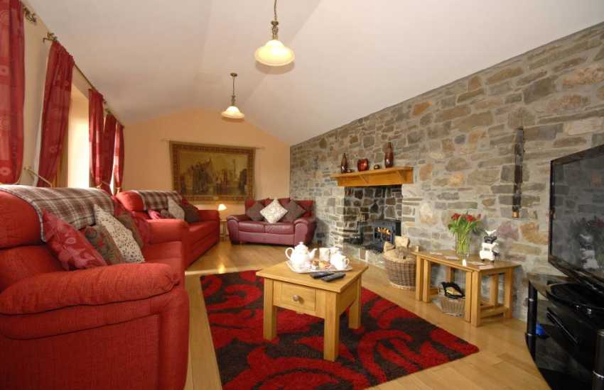Carmarthen Bay family holiday home - cosy sitting room with log burning stove