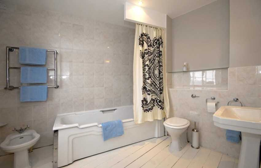 Tenby coastal holiday house - master en-suite bathroom with bidet and shower over bath