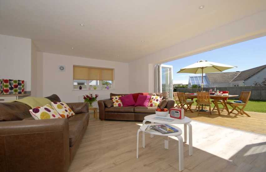 Whitesands self-catering home - open plan sitting room with bi-fold doors opening to deck and gardens