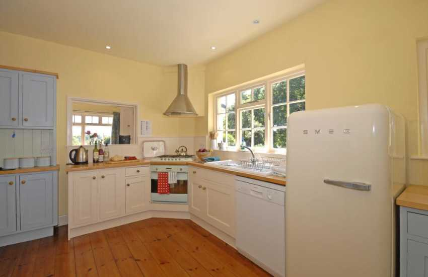 Self-catering Manorbier cottage - country style fitted kitchen with Smeg fridge