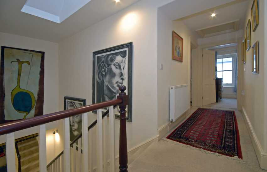 Hall staircase with large mirror and striking art works