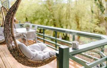 A chair swing sits on the terrace, looking across the Cotswold countryside