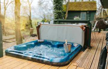 This electric hot tub for 4 sits on the wooden glamping cabins terrace